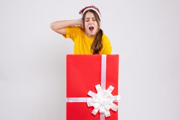 Вид спереди злая девушка в шляпе санта-клауса, держась за голову, стоя за большим рождественским подарком