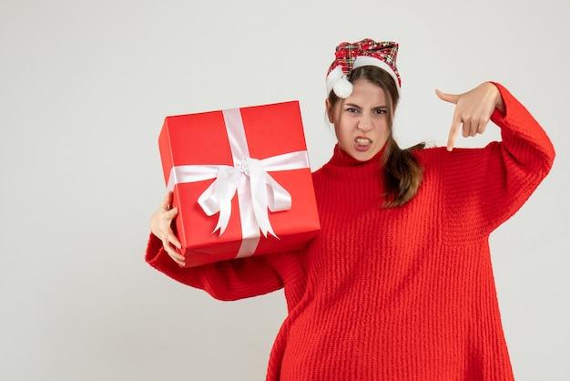산타 모자 서 아래로 가리키는 현재 손가락을 들고 전면보기 화가 소녀