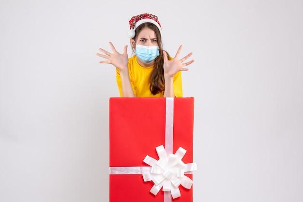 Вид спереди злая девушка в шляпе санта-клауса, открывая руки, стоя за большим рождественским подарком