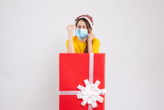 Вид спереди злая девушка в шляпе санта-клауса показывает удары, стоящие за большим рождественским подарком
