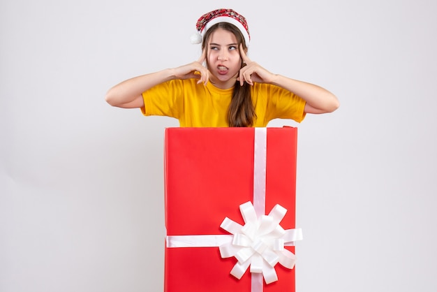 Front view angry girl with santa hat standing behind big xmas gift putting fingers