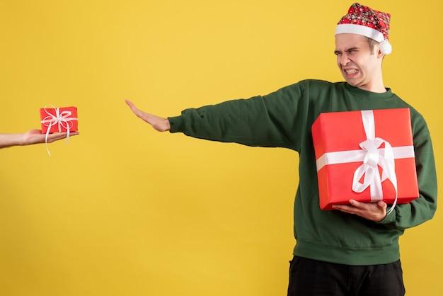 Vista frontale uomo arrabbiato chiudendo gli occhi rifiutando il dono in mano femminile su colore giallo