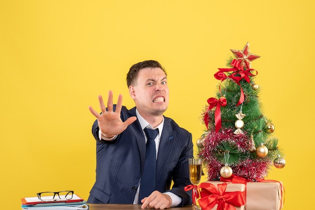 Front view angry man making stop sign sitting at the table near xmas tree and presents on yellow background