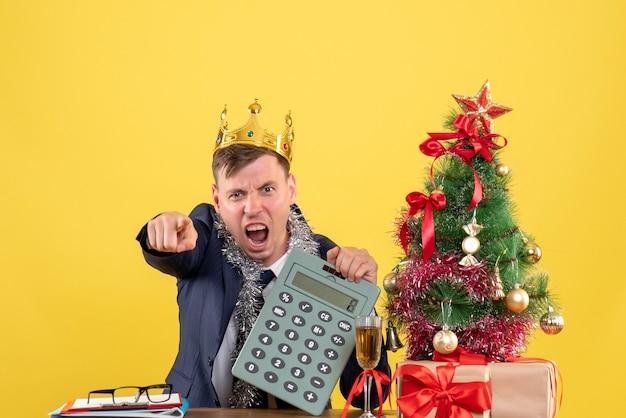 Vista frontale dell'uomo arrabbiato che indica alla macchina fotografica che si siede al tavolo vicino all'albero di natale e presenta sulla parete gialla