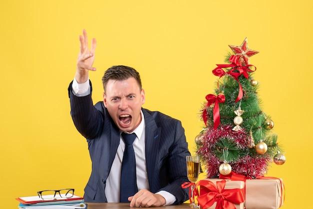 Vista frontale uomo arrabbiato che grida mentre era seduto al tavolo vicino all'albero di natale e regali su sfondo giallo