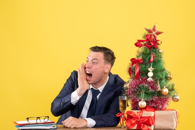 Front view angry man shouting while sitting at the table near xmas tree and presents on yellow background
