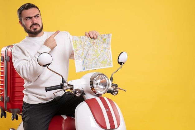 Front view of angry man sitting on motorcycle with suitcase on it holding map pointing up on isolated yellow background