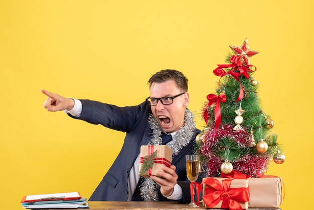 Front view angry man with eyeglasses sitting at the table near xmas tree and presents on yellow background