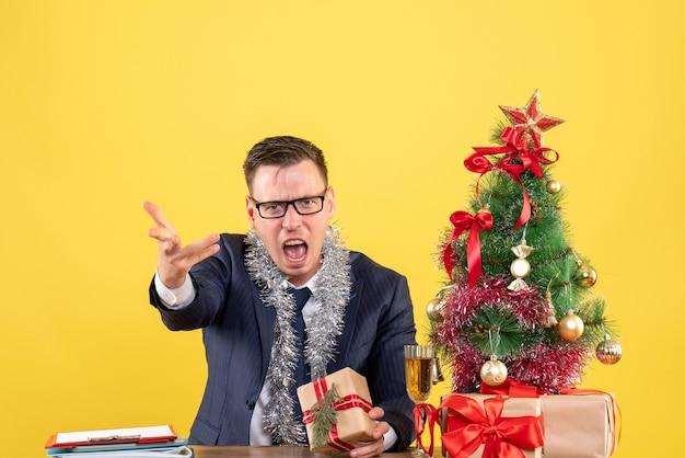 Vista frontale dell'uomo arrabbiato con gli occhiali seduto al tavolo vicino all'albero di natale e regali sulla parete gialla