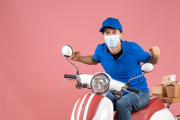 Vista frontale dell'uomo arrabbiato corriere nervoso in maschera medica che indossa cappello seduto su scooter su sfondo pesca pastello