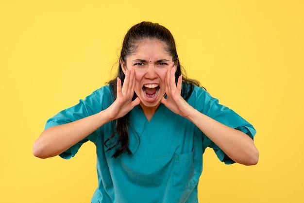 Medico femminile grazioso arrabbiato di vista frontale che grida su fondo giallo