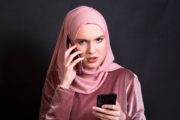 Front view of angry woman talking on cellphone against black background