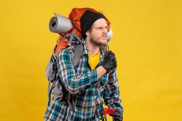 Vista frontale del giovane viaggiatore con zaino e sacco a pelo arrabbiato con la carta di credito della tenuta del cappello nero