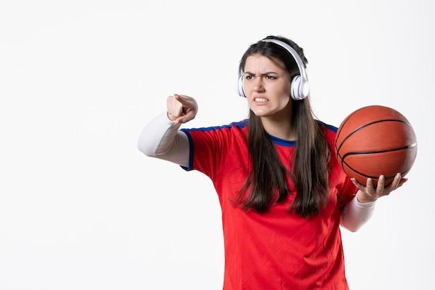 Giovane femmina arrabbiata di vista frontale in vestiti di sport con la pallacanestro