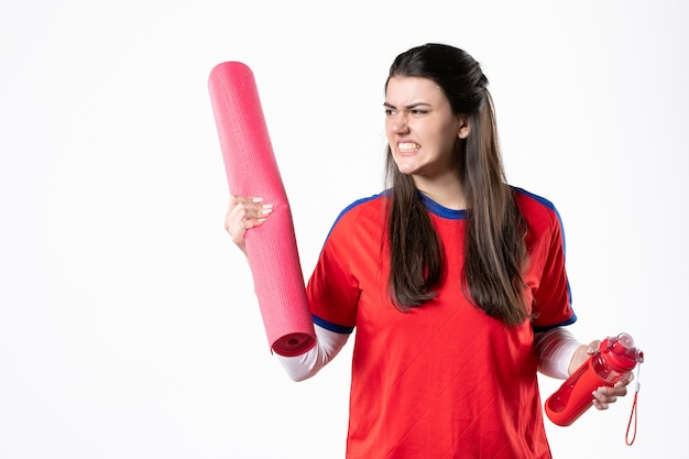 Front view angry young female in sport clothes with yoga mat