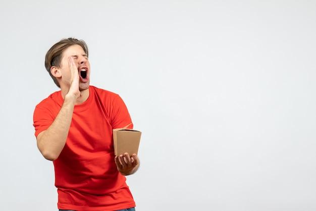 Vista frontale del giovane ragazzo arrabbiato in camicetta rossa che tiene piccola scatola e chiama qualcuno su priorità bassa bianca