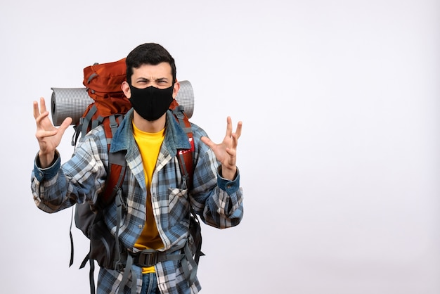 バックパックと手を上げるマスクと正面図怒っている若いハイカー