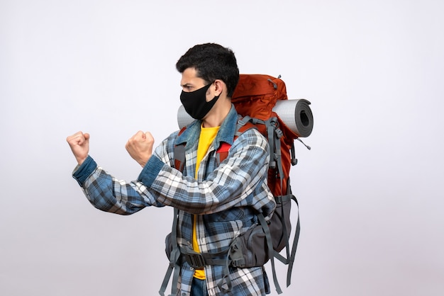 Front view angry young hiker with backpack and mask being ready to fight