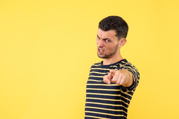 黒と白の縞模様のtシャツ黄色の孤立した背景の正面図怒っている若い男性