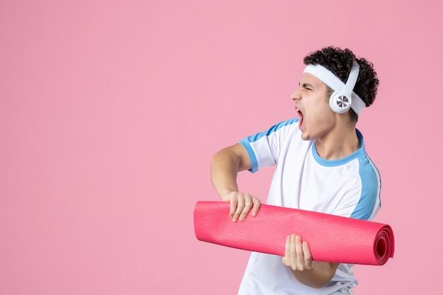 正面図ヨガマットとスポーツ服を着て怒っている若い男性