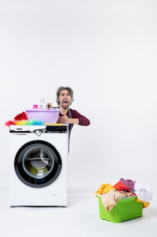 Front view angry young man in apron sitting behind washer laundry basket on white background