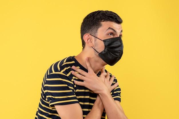 黒と白の縞模様のtシャツ黄色の背景で怒っている若者の正面図