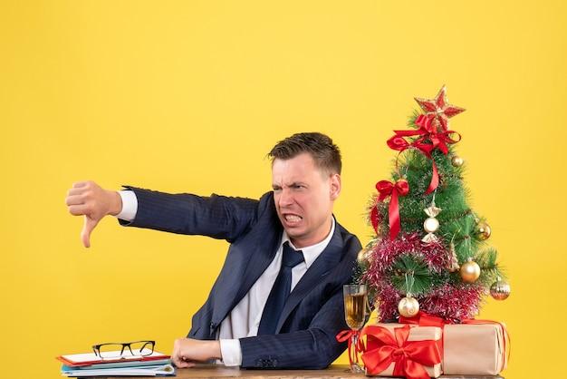 노란색 배경에 크리스마스 트리와 선물 근처 테이블에 앉아 기호 아래로 엄지 손가락을 만드는 전면보기 화가 젊은 남자