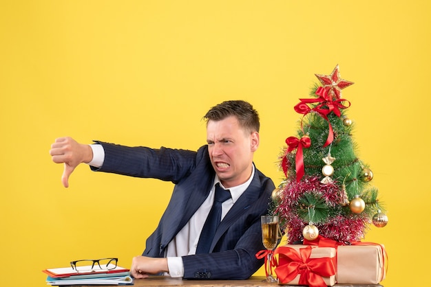 Front view angry young man making thumb down sign sitting at the table near xmas tree and gifts on yellow background