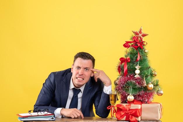 Вид спереди сердитый молодой человек, сидящий за столом возле рождественской елки и подарков на желтом фоне, свободное пространство