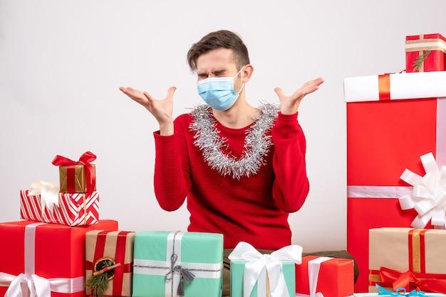 Вид спереди сердитый молодой человек с маской, открывающий руки, сидя вокруг рождественских подарков