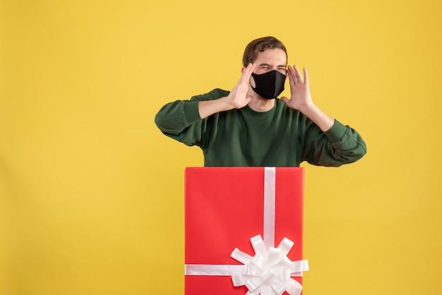 Вид спереди сердитого молодого человека с маской, стоящего за большой подарочной коробкой на желтом