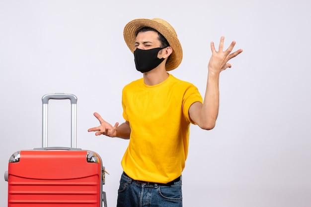 Вид спереди сердитый молодой человек с желтой футболкой и красным чемоданом