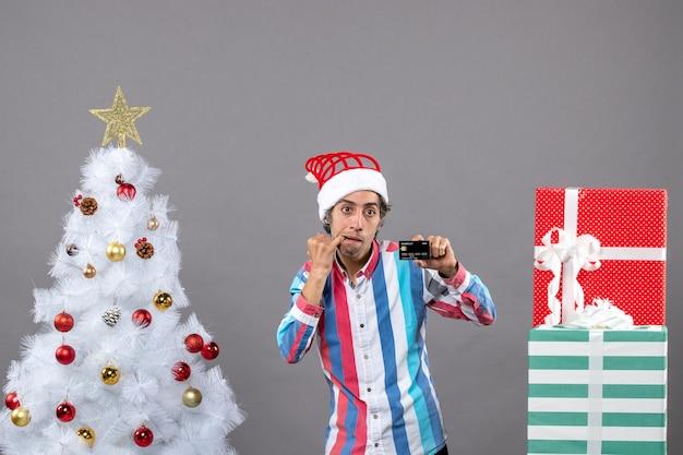 흰색 크리스마스 트리 근처에 서있는 그의 마우스에 손을 넣어 전면보기 냉담한 남자
