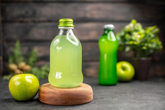 어두운 나무 표면에 나무 보드 레모네이드 사과에 병에 전면보기 사과 주스