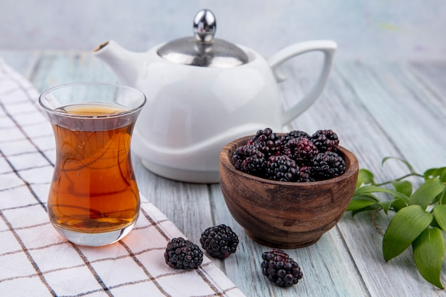 Front view of armudu glass of tea with teapot and blackberry on a gray surface