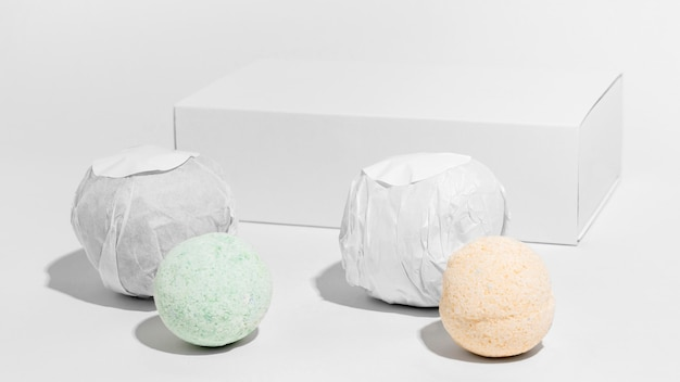 Front view arrangement of colored bath bombs on white background