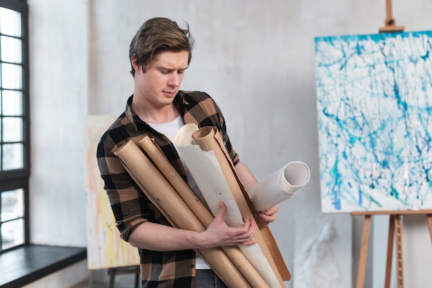 Вид спереди вычурный мужчина держит свои картины