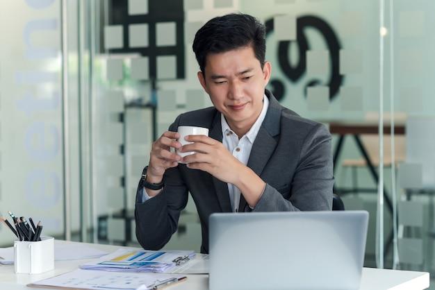 Вид спереди азиатский бизнесмен, пить кофе, глядя на ноутбук в офисе.
