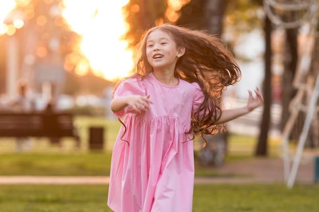 Азиатская маленькая девочка с длинными волосами, бегущая в парке, вид спереди