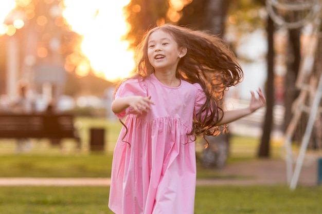Front view asian little girl with long hair running in the park