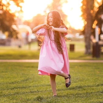Front view asian little girl with long hair walking in the park