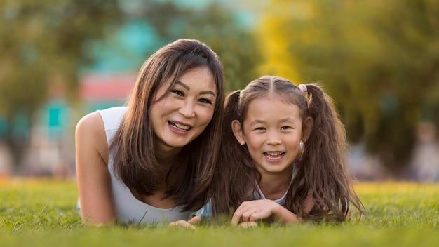 一緒に草の上に滞在アジアの母と娘の正面図