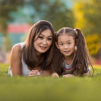 芝生の上に滞在アジアの母と娘の正面図