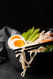 Front view of asian noodles with eggs and vegetables