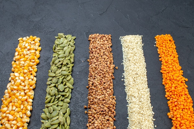 Front view of assorted grains of buckwheat pumpkin seeds corns rice on black background with free space