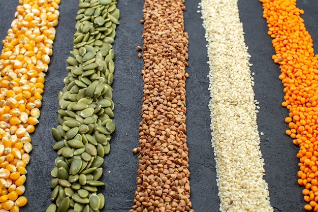 Front view of assorted grains of buckwheat pumpkin seeds corns rice on black background