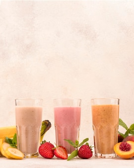 Front view of assortment of fruit milkshakes in glasses with copy space