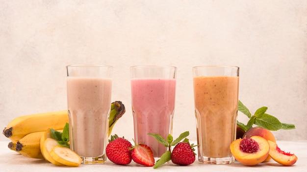Front view of assortment of fruit milkshakes in glasses