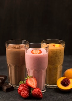 Front view of assortment of milkshakes with chocolate and fruits