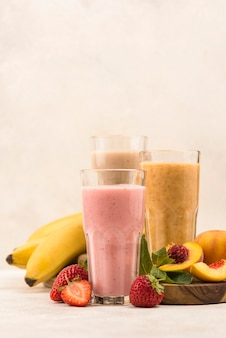 Front view of assortment of milkshakes with fruits and copy space